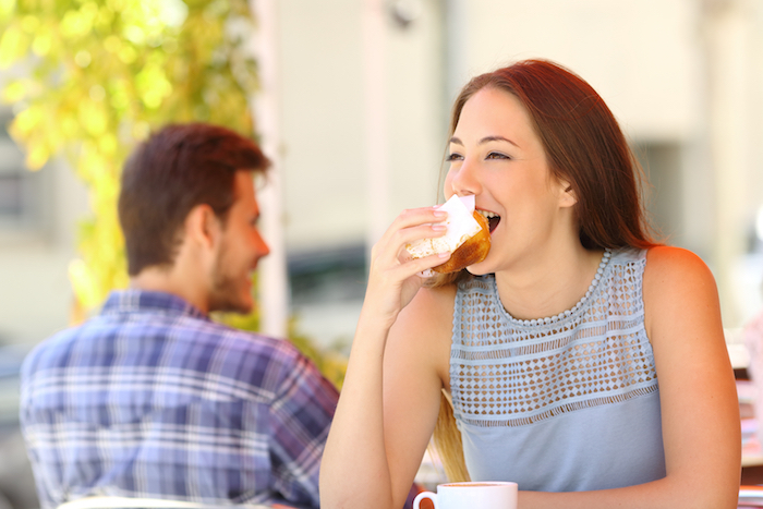 Woman eating a cupcake in a coffee shop